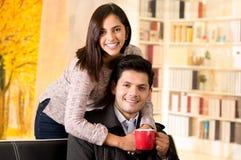 Beaux jeunes couples dans l'amour, femme embrassant son ami à un arrière-plan de bureau Photos libres de droits