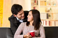 Beaux jeunes couples dans l'amour, homme embrassant son girfriend à un arrière-plan de bureau Photographie stock libre de droits