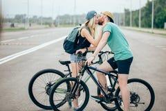Beaux jeunes couples dans l'amour marchant avec des bicyclettes, embrasser et étreindre Photo libre de droits