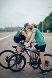 Beaux jeunes couples dans l'amour marchant avec des bicyclettes, embrasser et étreindre Photographie stock libre de droits