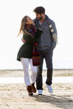 Beaux jeunes couples dans l'amour marchant en hiver froid sur le b Images libres de droits