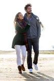 Beaux jeunes couples dans l'amour marchant en hiver froid sur le b Images stock