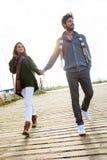 Beaux jeunes couples dans l'amour marchant en hiver froid sur le b Image stock