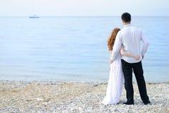 Beaux jeunes couples dans l'amour près de la mer Image libre de droits
