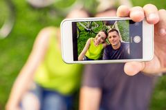 Beaux jeunes couples dans l'amour prenant le selfie en parc photos libres de droits