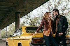 beaux jeunes couples dans l'amour regardant l'un l'autre tout en se tenant près du jaune Photographie stock