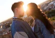 Beaux jeunes couples dans l'amour se tenant à un dessus de toit de bâtiment au coucher du soleil Image stock