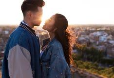 Beaux jeunes couples dans l'amour se tenant à un dessus de toit de bâtiment au coucher du soleil Image libre de droits