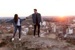 Beaux jeunes couples dans l'amour se tenant à un dessus de toit de bâtiment au coucher du soleil Photographie stock libre de droits