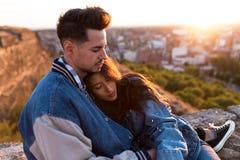 Beaux jeunes couples dans l'amour se tenant à un dessus de toit de bâtiment au coucher du soleil Photos libres de droits
