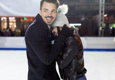 Beaux jeunes couples dans l'amour sur le patinage de glace dehors Image stock