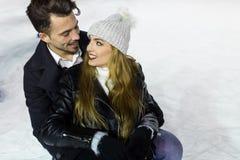 Beaux jeunes couples dans l'amour sur le patinage de glace dehors Photographie stock libre de droits