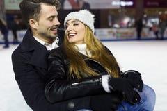Beaux jeunes couples dans l'amour sur le patinage de glace dehors Photo stock
