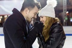 Beaux jeunes couples dans l'amour sur le patinage de glace dehors Photographie stock