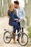 Beaux jeunes couples dans l'amour sur le vélo en parc Image libre de droits