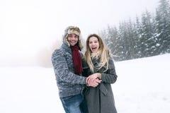 Beaux jeunes couples dans l'amour sur une promenade, nature d'hiver Photographie stock libre de droits