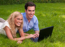Beaux, jeunes couples dans l'herbe avec l'ordinateur portatif images stock
