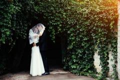 Beaux jeunes couples de mariage embrassant, jeune mariée blonde avec le flowe Photo stock