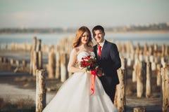 Beaux jeunes couples de mariage, jeunes mariés posant près des poteaux en bois sur la mer de fond Photos stock