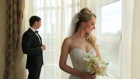 Beaux jeunes couples de mariage se tenant près de la fenêtre Proue d'étoile bleue avec la bande bleue (enveloppe de cadeau) sur l banque de vidéos