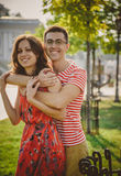 Beaux jeunes couples de sourire dans l'amour, étreignant et passant le temps ensemble dehors à la rue verte de ville Photographie stock libre de droits