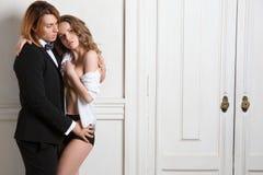 Beaux jeunes couples de sourire dans l'embrassement d'amour d'intérieur Photos libres de droits