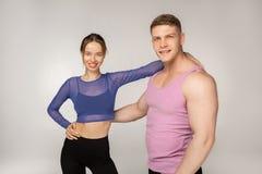 Beaux jeunes couples de sourire dans les vêtements de sport à la mode photos stock