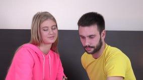 Beaux jeunes couples de sourire prenant le petit déjeuner dans le lit, plan rapproché clips vidéos