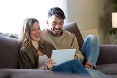 Beaux jeunes couples de sourire utilisant leur comprimé numérique au hom photographie stock