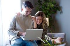 Beaux jeunes couples de sourire utilisant leur ordinateur portable à la maison Images stock