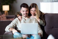 Beaux jeunes couples de sourire utilisant leur ordinateur portable à la maison Photographie stock libre de droits