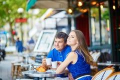 Beaux jeunes couples des touristes en café parisien de rue Image libre de droits