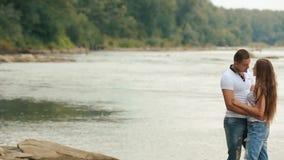 Beaux jeunes couples embrassant près de la grande rivière sur la banque en pierre clips vidéos