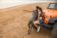 Beaux jeunes couples embrassant tout en se penchant sur leur voiture Images stock