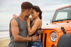 Beaux jeunes couples embrassant tout en se tenant près de leur voiture Photo stock