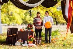 Beaux jeunes couples enceintes ayant le pique-nique dans le parc d'automne Ha Photographie stock