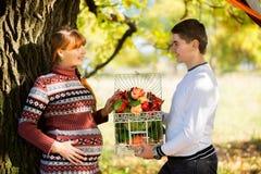Beaux jeunes couples enceintes ayant le pique-nique dans le parc d'automne Ha Photo libre de droits