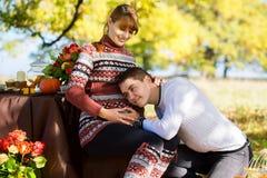 Beaux jeunes couples enceintes ayant le pique-nique dans le parc d'automne Ha Photo stock