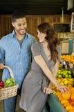 Beaux jeunes couples faisant des emplettes ensemble sur le marché Image libre de droits