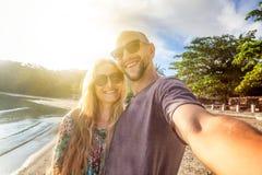 Beaux jeunes couples faisant le selfie sur la plage, vacances, holi Image libre de droits
