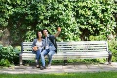 Beaux jeunes couples faisant un selfie en parc Photo libre de droits