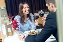 Beaux jeunes couples grillant des verres de vin dans le restaurant Photo stock