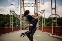 Beaux jeunes couples heureux de la rotation de l'homme et de femme extérieure sur le pont Images stock