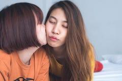 Beaux jeunes couples heureux lesbiens asiatiques des femmes LGBT se reposant sur le lit étreignant et souriant ensemble dans la c Images libres de droits