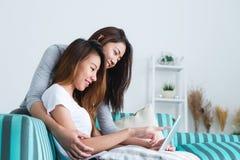 Beaux jeunes couples heureux lesbiens asiatiques des femmes LGBT se reposant sur le sofa achetant en ligne utilisant le comprimé  Image stock