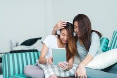 Beaux jeunes couples heureux lesbiens asiatiques des femmes LGBT se reposant sur le sofa achetant en ligne utilisant le comprimé  Images stock