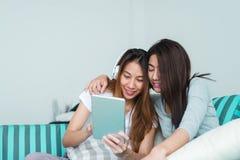 Beaux jeunes couples heureux lesbiens asiatiques des femmes LGBT se reposant sur le sofa achetant en ligne utilisant le comprimé  Photos libres de droits