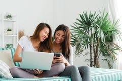 Beaux jeunes couples heureux lesbiens asiatiques des femmes LGBT se reposant sur le sofa achetant en ligne utilisant l'ordinateur Photos libres de droits