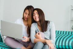 Beaux jeunes couples heureux lesbiens asiatiques des femmes LGBT se reposant sur le sofa achetant en ligne utilisant l'ordinateur Photos stock