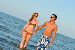 Beaux jeunes couples heureux marchant tenant des mains sur le bord de la mer Images stock